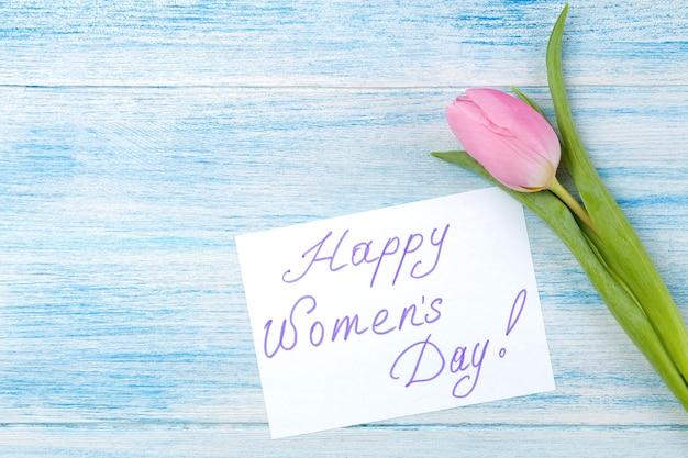 Hermosa flor rosa tulipán y texto feliz día de la mujer sobre una superficie de madera azul