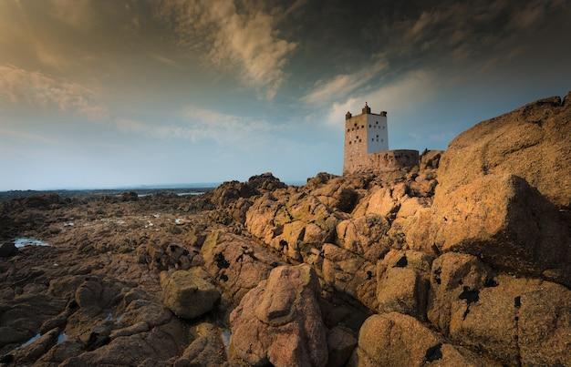 Hermosa foto de acantilados y rocas con una fortaleza en la parte superior bajo un cielo azul