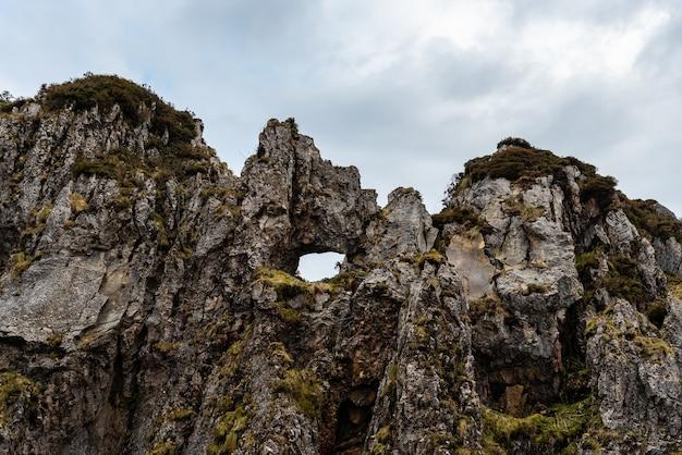 Hermosa foto de acantilados rocosos en un día lluvioso cerca de la playa