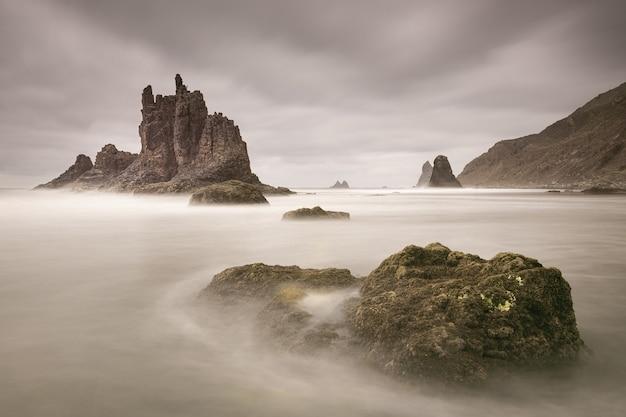 Hermosa foto de agua que fluye alrededor de grandes piedras cerca de la roca de benijo en un día nublado en españa