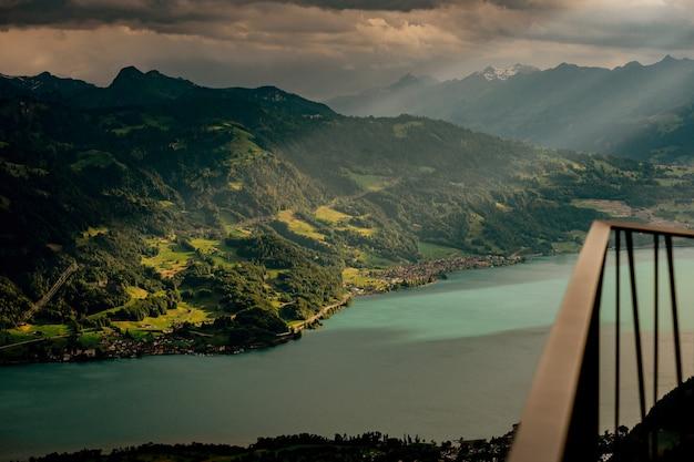Hermosa foto de altas montañas cubiertas de plantas verdes cerca del lago bajo las nubes de tormenta