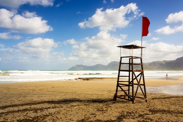Hermosa foto de un asiento de salvavidas de playa con una bandera roja en mallorca