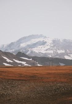 Hermosa foto de un campo fangoso con increíbles montañas nevadas