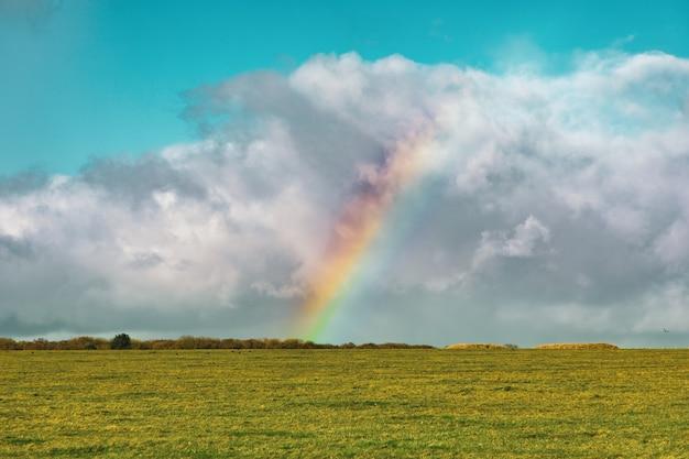 Hermosa foto de un campo de hierba vacío con un arco iris en la distancia bajo un cielo nublado azul