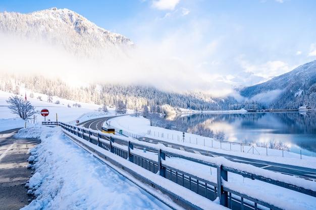 Hermosa foto de una carretera cerca de un lago rodeado de montañas cubiertas de nieve.