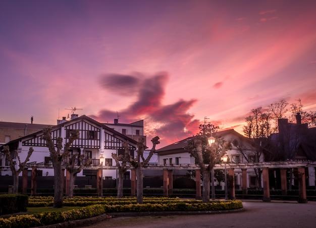 Hermosa foto de casas en pamplona, españa, con un paisaje de puesta de sol en el fondo