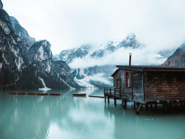 Hermosa foto de una casita de madera junto a un lago en un muelle con increíbles montañas nubladas y nevadas