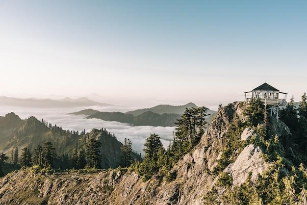 Hermosa foto de un cenador blanco en la cima de la montaña cerca de los árboles con un cielo despejado en segundo plano.