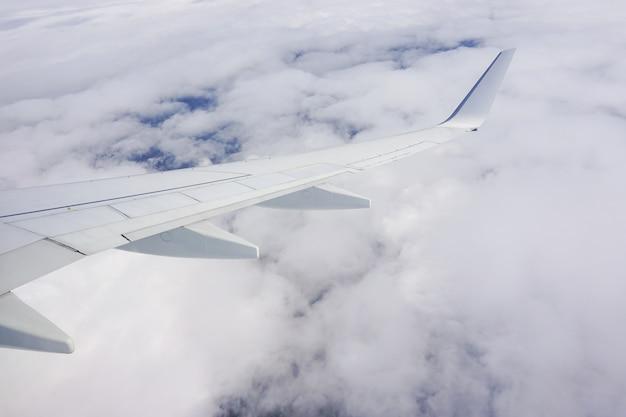 Hermosa foto del cielo lleno de nubes y un ala de avión desde la ventana del avión