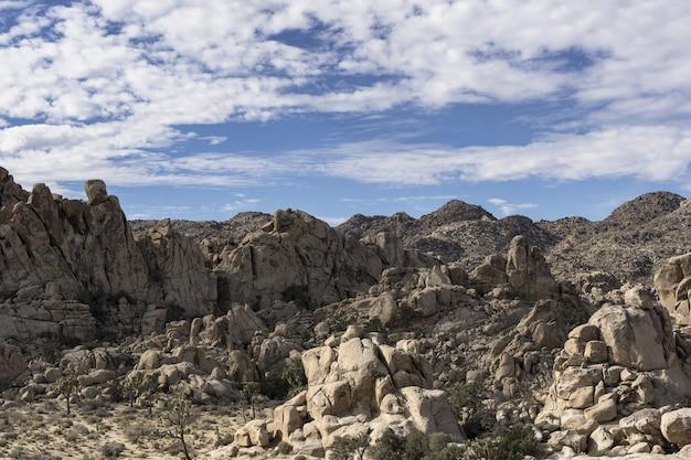 Hermosa foto de colinas rocosas y montañas bajo un cielo azul nublado durante el día