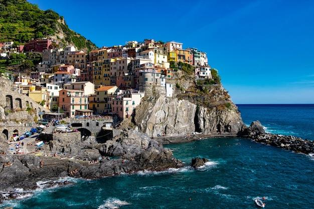 Hermosa foto de coloridos edificios de apartamentos en una colina rocosa en la orilla del mar bajo el cielo azul