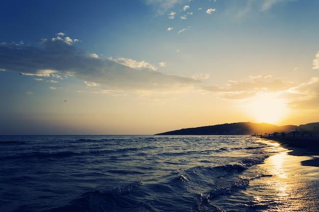 Hermosa foto de la costa arenosa del mar con una increíble puesta de sol
