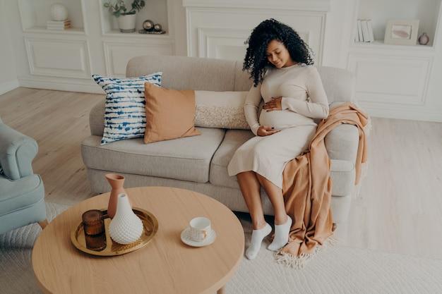 Hermosa foto dama afroamericana sentada en un sofá acogedor y esperando un bebé mirando hacia abajo en su campana