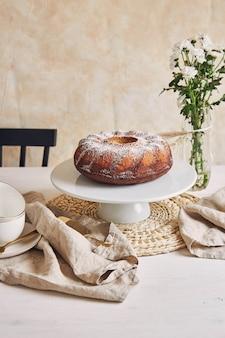 Hermosa foto de un delicioso pastel de anillo puesto en un plato blanco y una flor blanca cerca