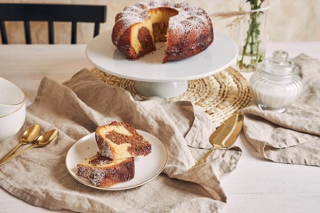 Hermosa foto de un delicioso pastel de anillo puesto en un plato blanco y una flor blanca cerca de él