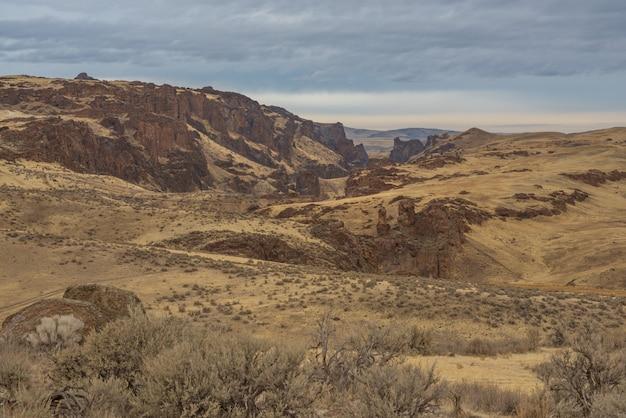 Hermosa foto de un desierto con montañas cubiertas de arbustos secos bajo un cielo nublado azul