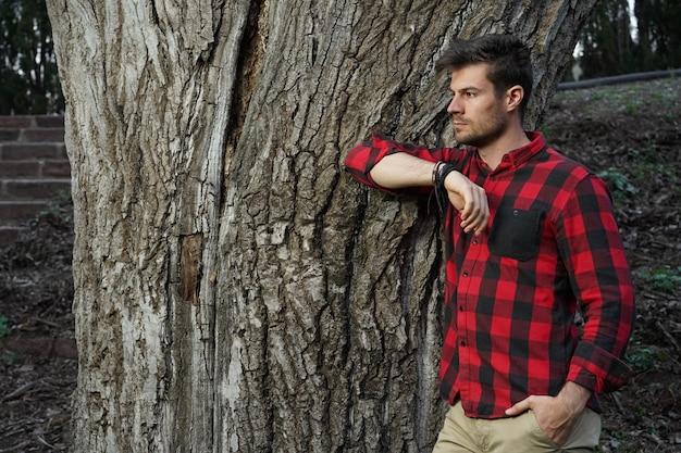 Hermosa foto de un encantador joven apoyado en un viejo árbol grueso con la mano