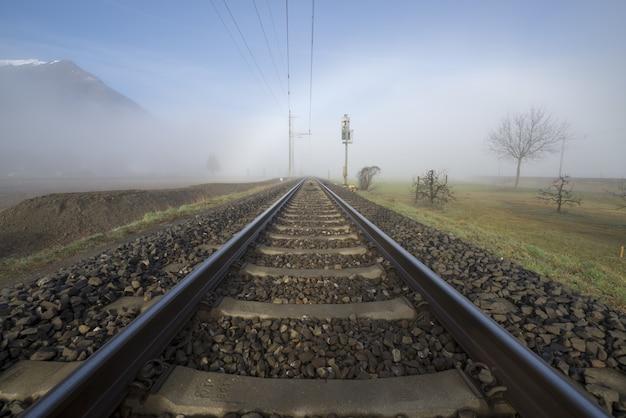 Hermosa foto de un ferrocarril con una niebla blanca