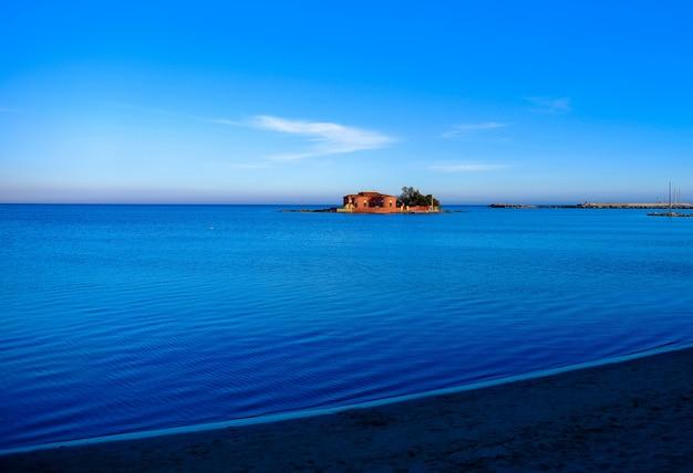 Hermosa foto de una gran casa en medio del mar bajo un cielo azul