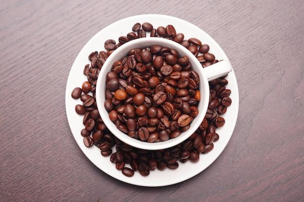 Hermosa foto de granos de café en la taza blanca y el plato sobre una mesa de madera