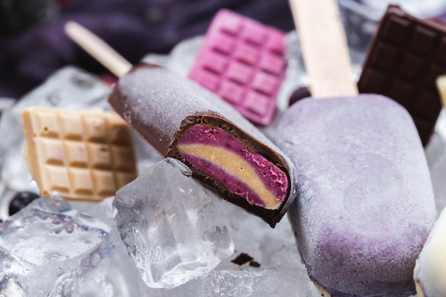 Hermosa foto de helados veganos caseros y barras de chocolate sobre hielo