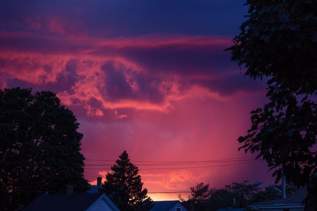 Hermosa foto de la hermosa puesta de sol púrpura oscuro en el campo
