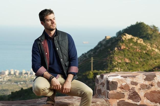 Hermosa foto de un hombre exitoso posando frente a su casa con una vista perfecta de la ciudad detrás