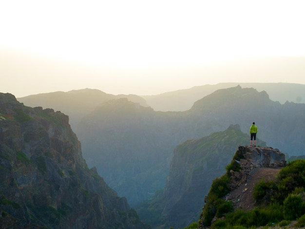 Hermosa foto de un hombre de pie en el borde de un acantilado con vistas a las montañas sombreadas debajo