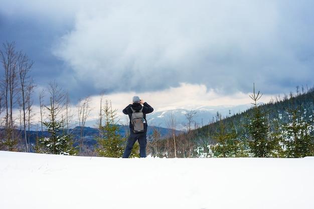 Hermosa foto de un hombre tomando una foto de montañas boscosas nevadas