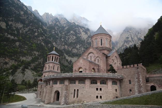 Hermosa foto de una iglesia cristiana con árboles y montañas en georgia