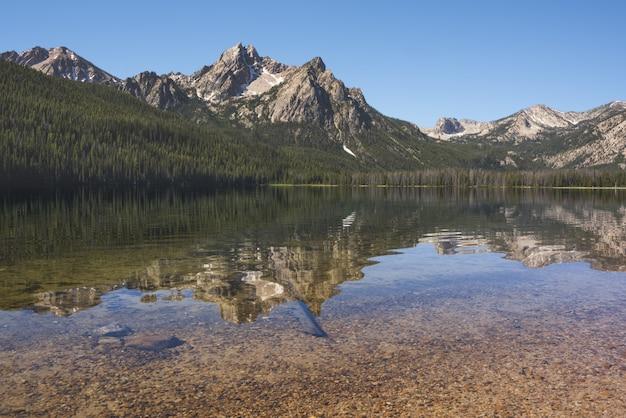 Hermosa foto del lago que refleja los árboles y las montañas en la orilla bajo un cielo azul claro
