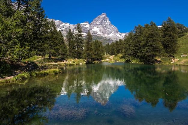 Una hermosa foto de un lago que refleja los árboles en la orilla con una montaña nevada