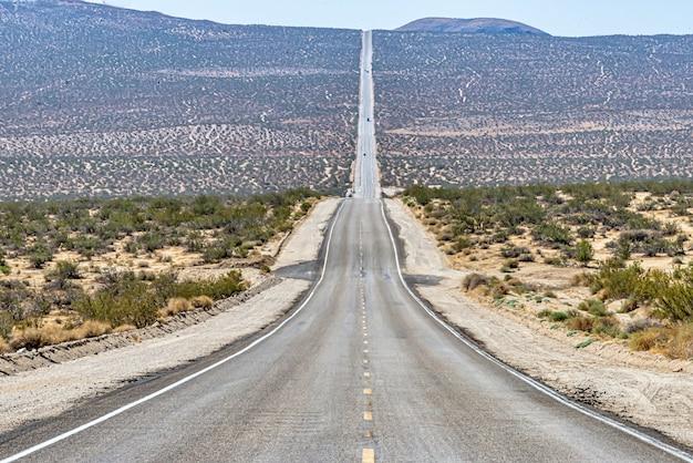 Hermosa foto de un largo camino de hormigón recto entre el campo del desierto