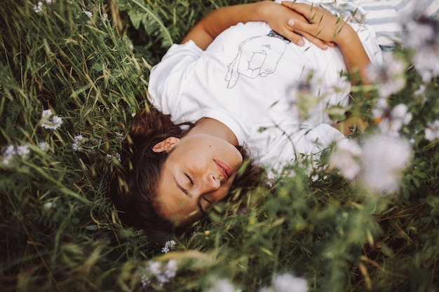 Hermosa foto de una modelo que se establecen en un campo de margaritas con los ojos cerrados