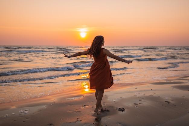 Hermosa foto de una modelo con un vestido marrón disfrutando de la puesta de sol en la playa