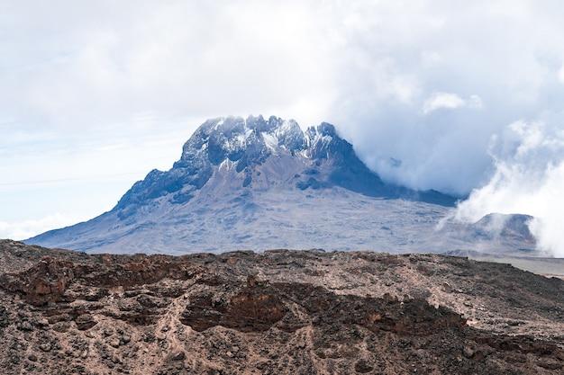 Hermosa foto de una montaña con las nubes creando una atmósfera brumosa