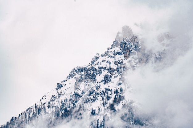 Hermosa foto de una montaña nublada cubierta de nieve con cielo gris