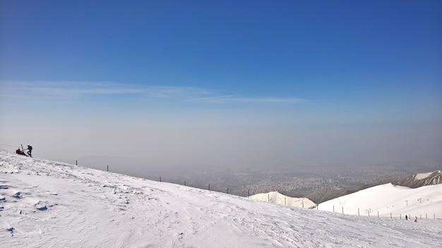 Hermosa foto de montañas nevadas y dos personas a la izquierda