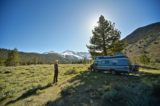 Hermosa foto de una mujer de pie en un campo de hierba cerca de una camioneta con montaña