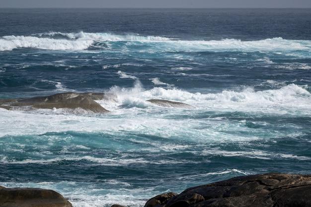 Hermosa foto del océano ondulado con algunas piedras en el agua