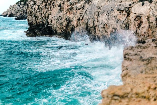 Hermosa foto de las olas del mar golpeando la costa rocosa, perfecta para el fondo
