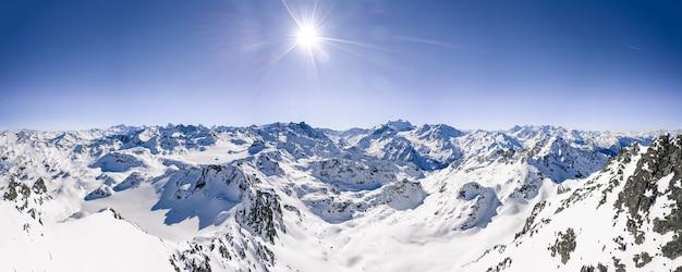 Hermosa foto panorámica de cadenas montañosas cubiertas de nieve bajo un cielo soleado azul claro
