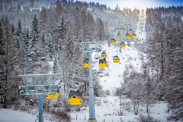 Hermosa foto panorámica de una larga fila de teleféricos en la pista de esquí