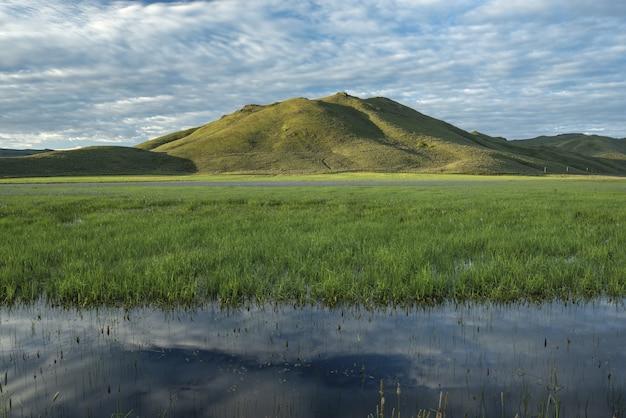 Hermosa foto de pantano de agua dulce con una montaña verde y un cielo azul nublado en el