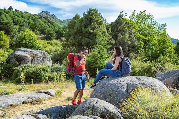 Hermosa foto de una pareja feliz sentada en la roca mientras disfruta del fresco