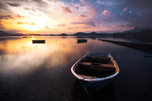 Hermosa foto de un pequeño lago con un bote de remos de madera en foco y nubes increíbles en el cielo