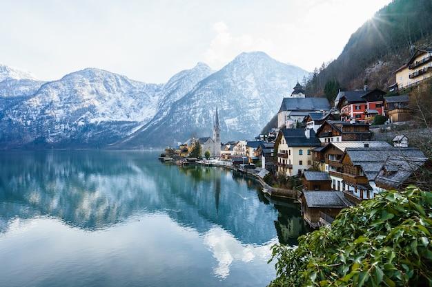 Hermosa foto de un pequeño pueblo rodeado por un lago y colinas nevadas