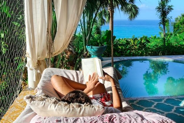 Hermosa foto de una persona acostada en el diván leyendo un libro cerca de una piscina con plantas tropicales