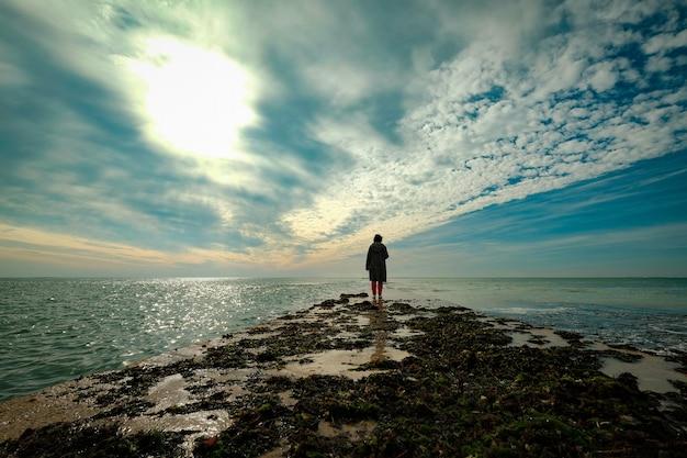 Hermosa foto de una persona caminando sobre una tierra dentro del océano bajo el cielo nublado