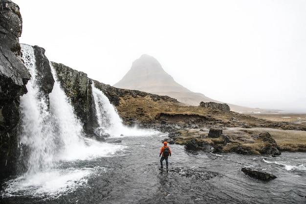 Hermosa foto de una persona de pie en el agua cerca de cascadas que fluyen por las colinas